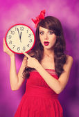 Beautiful brunette girl with big clock on violet background. — Stock Photo