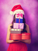 Beautiful brunette girl in christmas hat with gifts  on violet b — Stock Photo