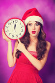Beautiful brunette girl in christmas hat with huge clock on viol — Stock Photo