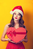 Beautiful brunette girl in christmas hat with gift on yellow bac — Stock Photo