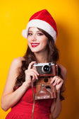 Beautiful brunette girl in christmas hat with camera on yellow b — Stock Photo