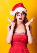 Beautiful brunette girl in christmas hat with glasses on yellow  — Foto Stock