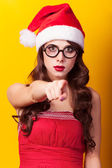 Beautiful brunette girl in christmas hat with glasses on yellow  — Stock fotografie