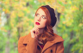 Redhead girl in autumn park — Stock Photo