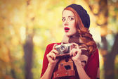 Redhead women in beret with camera in the park — Stock Photo