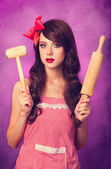 Beautiful brunette housewife with rolling pin on violet backgrou — Stock Photo