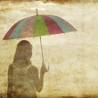 Girl with umbrella at sea coast. Photo in old image style. — Stock Photo #6024004