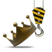 Yellow crane hook lifting golden crown — Stock Photo