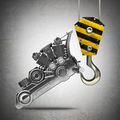 Yellow crane hook lifting chromed motorcycle engine — Stock Photo