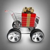 Shopping cart with big car wheel and RED christmas gift — Stock Photo