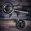 Antique brass compass and magnifying glass — Stock Photo #32125327