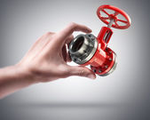 Hand holding red valve — Stock Photo