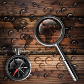 Antique brass compass and magnifying glass — Stock Photo