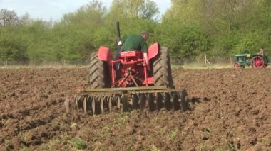 Red vintage tractor pulling a disk harrow. — Stock Video