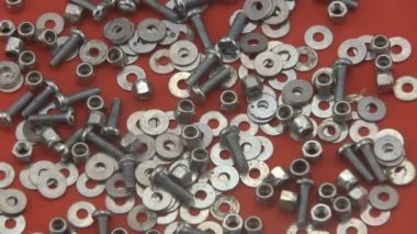 Nuts, washers and bolts rotating on a red background. — Stock Video