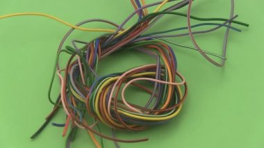 Multicoloured six amp electrical wire rotating on a green background. — Stock Video