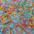 Close up of colourful rubber bands on a blue background — Stock Photo #50580563