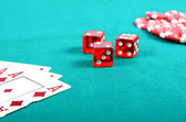 Red poker gambling chips,dices and few aces on a green playing table — Stok fotoğraf