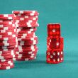 Red poker gambling chips on a green playing table — Stock Photo