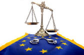 Scales of Justice, European Union flag and handcuffs — Stock Photo