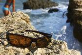 Sluneční brýle na kamenné pobřeží — Stock fotografie