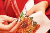 Embroidery process on fabric beads hands — Stock Photo
