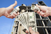 Hands  with notes  dollars against the house under construction — Stock Photo