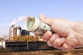 Mano dell'uomo con dollari di note contro la fabbrica — Foto Stock
