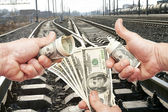 Hands with notes of dollars against the railroad — Stock Photo
