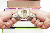 Dollars  in a hand against with books — Stock Photo