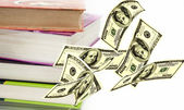 Falling notes of US dollar near books  — Stock Photo
