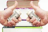 Hand with notes of US dollars against books — Stock Photo