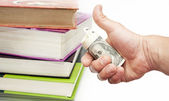 Books and hand with US dollar notes  — Stock Photo