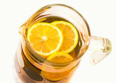 Cooling lemonade with lemon slices in a glass jug — Stock Photo