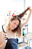 Young girl taking care of her hairs in a bathroom — Stock Photo