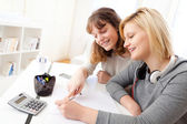 Young teacher assist a student during her homework — Stock Photo