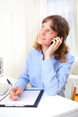 Young attractive business woman copying data on paper while phon — Stock Photo