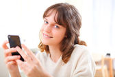 Portrait of young smiling woman writing a text — Stock Photo