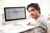 Young smiling man in front of computer — Stock Photo