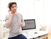 Young relaxed man listenning music at the office — Foto de Stock