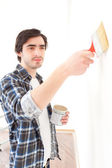 Attractive young man painting a wall in his new flat — Stock Photo