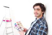 Attractive young man choosing the color of his flat — Stok fotoğraf