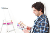 Attractive young man choosing the color of his flat — ストック写真