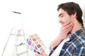 Attractive young man choosing the color of his flat — Stock Photo