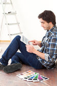 Young man using tablet while choosing color of his flat — Stok fotoğraf