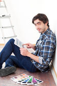 Young man using tablet while choosing color of his flat — Stock Photo