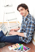 Young man using laptop while choosing color of his flat — Stock Photo