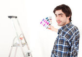 Attractive young man choosing color of his flat — Stock Photo
