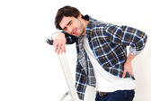 Young man suffering while working on a stepladder — Stock Photo