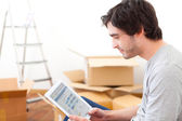 Handsome young man in his new flat using tablet — Stock Photo